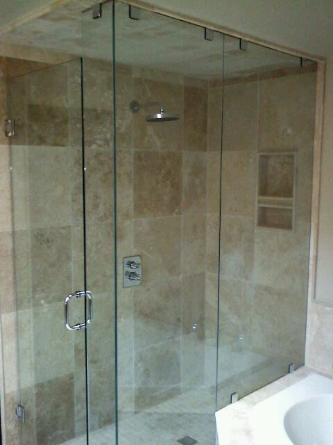 a 90 degree frameless shower with chrome hinges and door handle